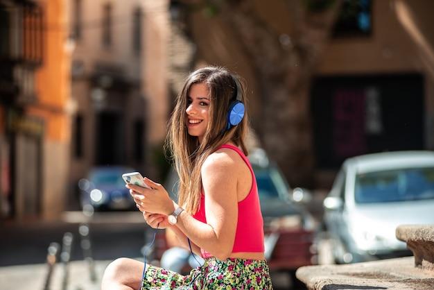 도시에있는 계단에 앉아 긴 머리를 가진 젊은 금발 소녀. 웃고 그녀의 휴대 전화와 헤드폰으로 음악을 듣고.