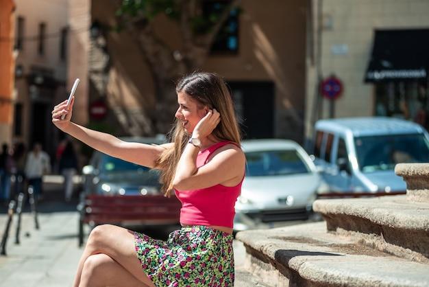 도시에있는 계단에 앉아 긴 머리를 가진 젊은 금발 소녀. 그녀의 휴대폰으로 셀카를 찍습니다.