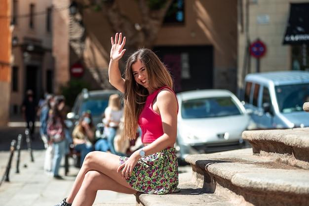 친구를 인사하는 동안 계단에 앉아 긴 머리를 가진 젊은 금발 소녀.
