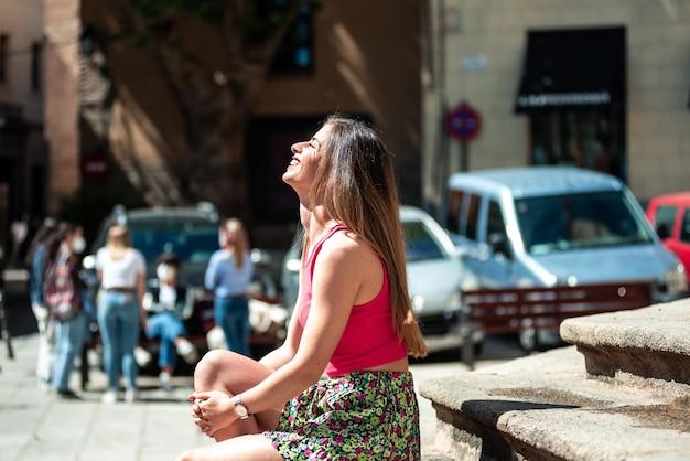 화창한 날을 즐기면서 도시의 돌 계단에 앉아 긴 머리를 가진 젊은 금발 소녀.