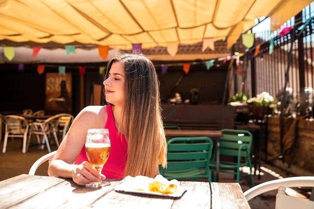 바의 테라스에서 맥주와 일부 칩을하면서 웃 고 긴 머리를 가진 젊은 금발 소녀.
