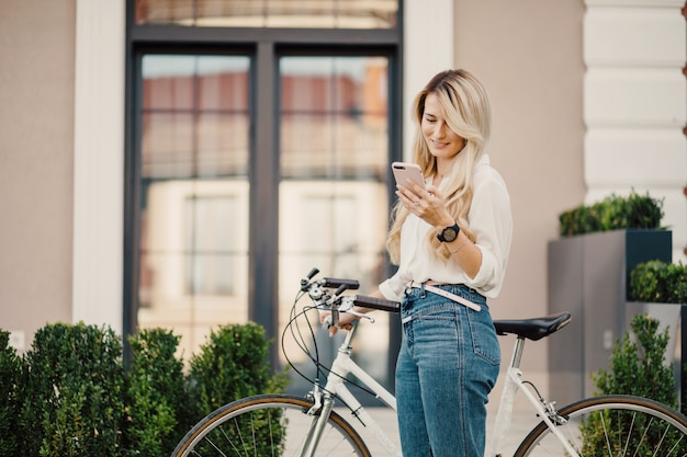 Young blonde girl with long hair standing near vintage white bicycle.