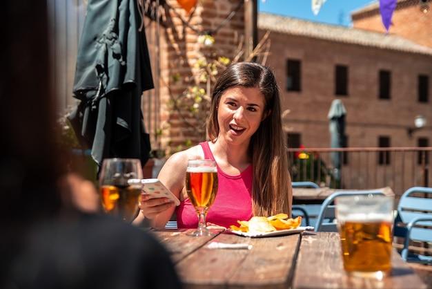 바의 테라스에서 맥주를 마시면서 친구에게 이야기하는 긴 머리를 가진 젊은 금발 소녀.