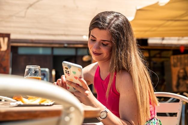 바의 테라스에서 맥주와 일부 칩을 마시면서 그녀의 휴대 전화를 사용하여 긴 머리를 가진 젊은 금발 소녀. 프리미엄 사진