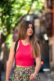 도시에서 걷는 긴 머리를 가진 젊은 금발 소녀. 프리미엄 사진