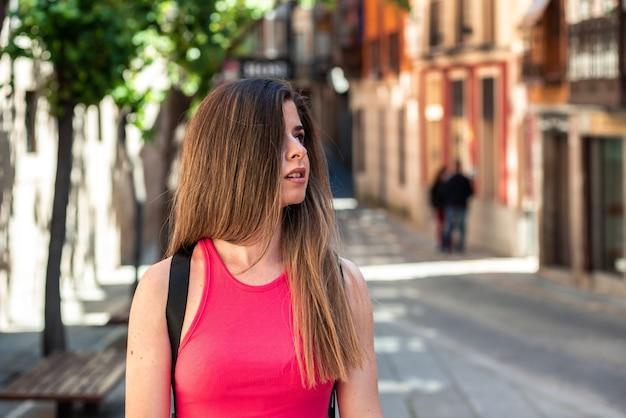도시에서 걷는 긴 머리를 가진 젊은 금발 소녀.