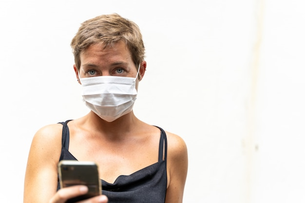 Young blonde girl with a mask on her face to protect her from viruses and a mobile phone