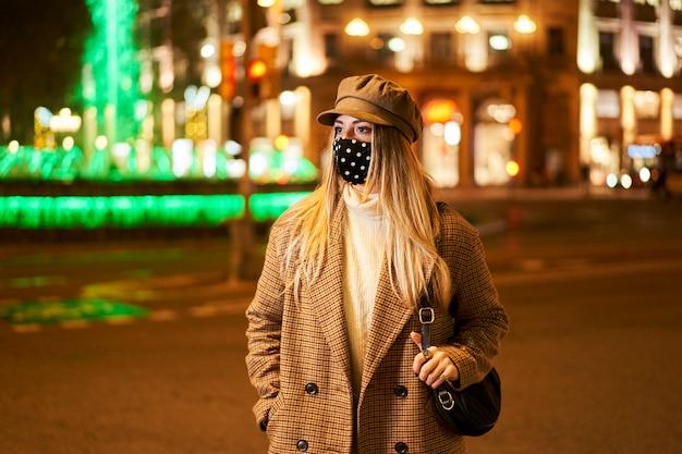 마스크 측면을 찾고 젊은 금발 소녀. 그녀는 밤에 도시에 있습니다. 겨울 분위기.