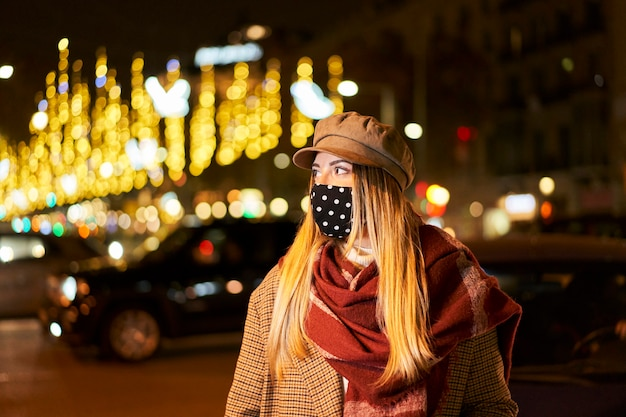 Молодая блондинка с маской, глядя в сторону. она находится в ночном городе с множеством фонарей и проезжающих машин. зимняя атмосфера.