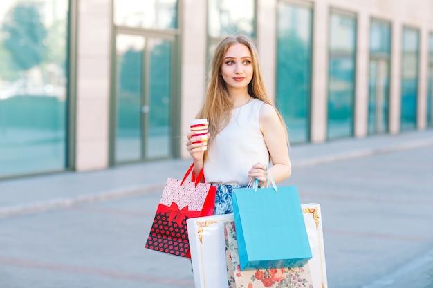 쇼핑 가방가 게에서 밖으로 걸어 젊은 금발 소녀.