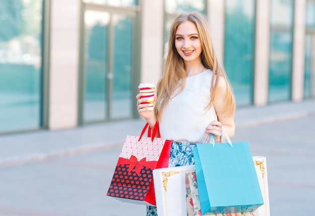 Young blonde girl, with shopping bags walking out from shop.