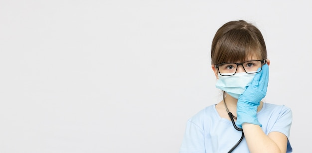 Young blonde girl with toothache in medical mask banner copy space