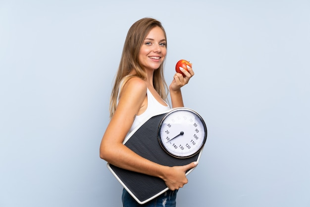 Young blonde girl with weighing machine and with an apple