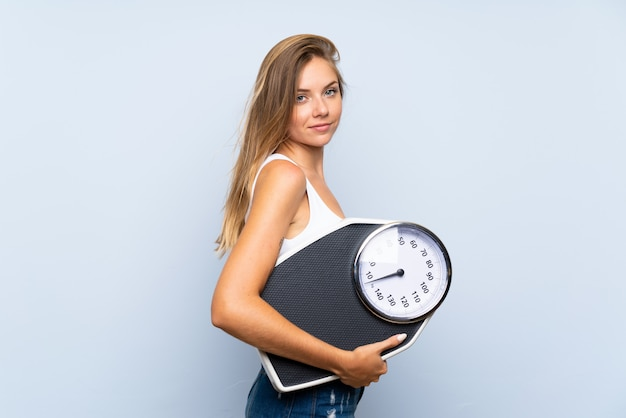 Young blonde girl with weighing machine