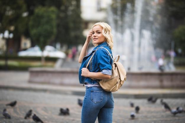 Молодая блондинка женщина на уличном фонтане, одетая в синие джинсы с сумкой на плече в солнечный день