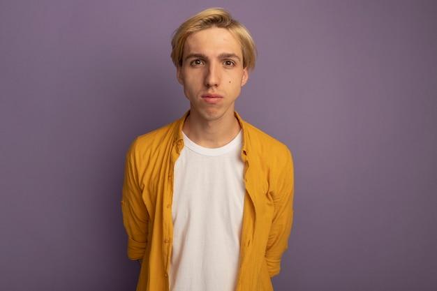Молодой блондин смотрит прямо перед собой в желтой футболке, держась за руки на талии, изолированной на фиолетовом