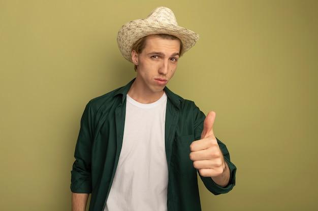 녹색 t- 셔츠와 엄지 손가락을 보여주는 모자를 쓰고 젊은 금발의 남자