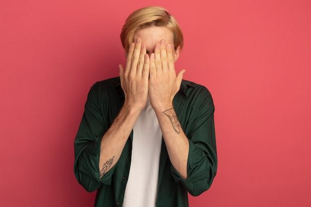 緑のtシャツを着ている若いブロンドの男は手で顔を覆った