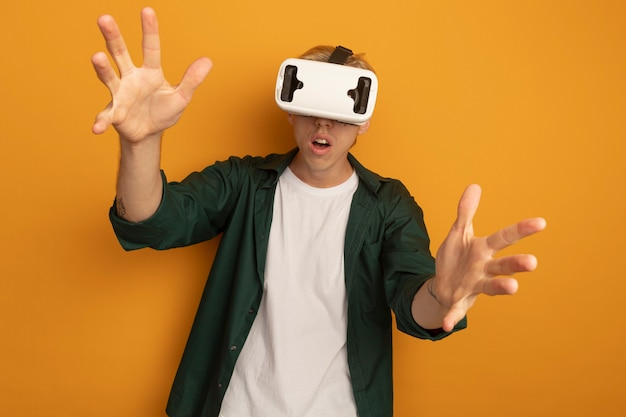 Young blonde guy wearing green t-shirt and vr headset spreading hands