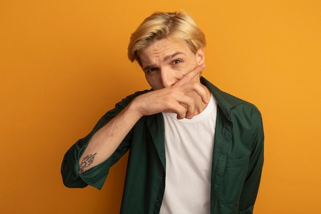 손으로 코를 닦아 녹색 티셔츠를 입고 젊은 금발의 남자