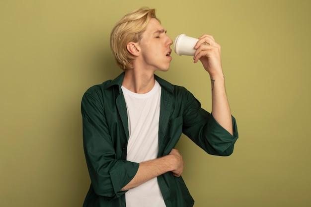 緑のtシャツを着て目を閉じて若い金髪の男はコーヒーを飲む