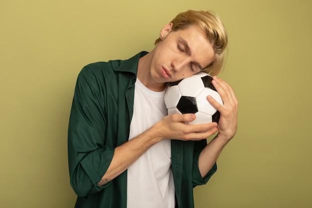 Giovane ragazzo biondo con gli occhi chiusi che indossa la sfera della tenuta della maglietta verde sulla guancia