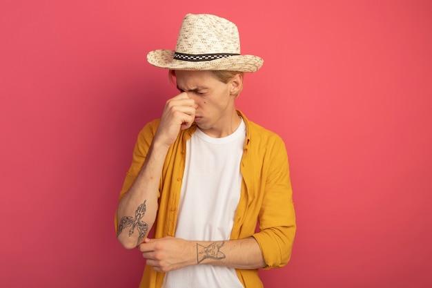 目を閉じて黄色のtシャツと帽子をかぶった若いブロンドの男はピンクで隔離の鼻をつかんだ