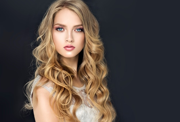 長く、波打つ、手入れの行き届いた、縮れた髪の若いブロンドの髪の美しいモデル。自由に横たわるカールのあるスタイリッシュでルーズなヘアスタイル。理髪アート、ヘアケア、メイクアップ。