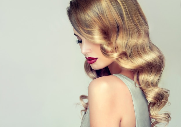 Young, blonde haired woman with elegant, voluminous evening hairstyle. profile of woman framed by shiny curls of bonde hair.hairdressing art, hair care and makeup.