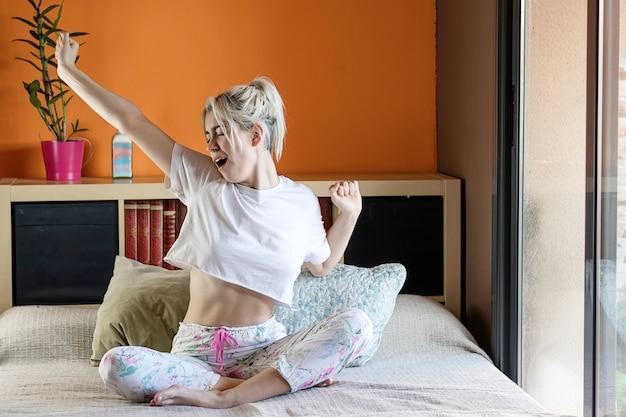 Молодая блондинка счастливая улыбающаяся женщина просыпается