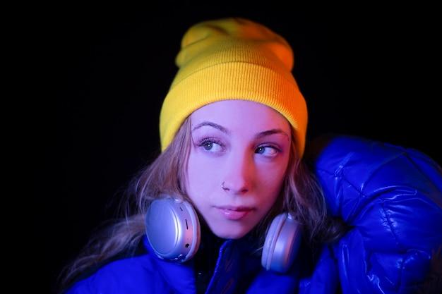 暗い場所で夜に音楽を聴いて若い金髪の幸せな十代の少女