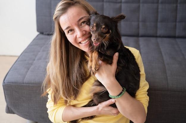 Молодая блондинка счастливая женщина в желтом свитере держит смешной коричневый русский игрушечный терьер. концепция ухода за домашними животными.