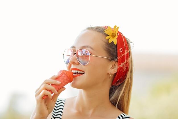 サングラスで夏の暑い天気でおいしいピンクのアイスクリームを食べる若い金髪の流行に敏感な女の子は、楽しくて良い気分と笑顔を持っています。