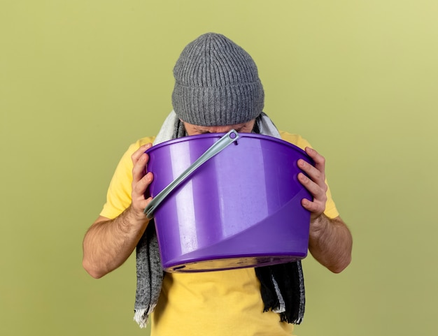 冬の帽子とスカーフを身に着けている若い金髪の病気のスラブ人は、コピースペースでオリーブグリーンの壁に吐き気を分離したプラスチック製のバケツを保持 無料写真