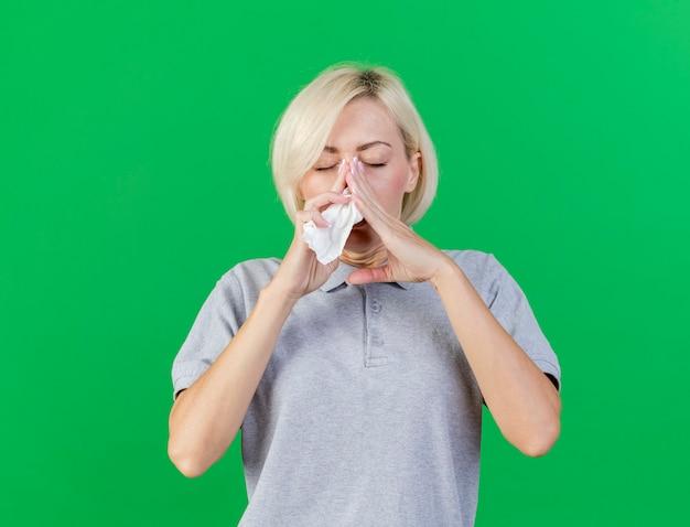 若い金髪の病気のスラブ女性は、コピースペースで緑の壁に分離された組織を保持している鼻に手を置きます