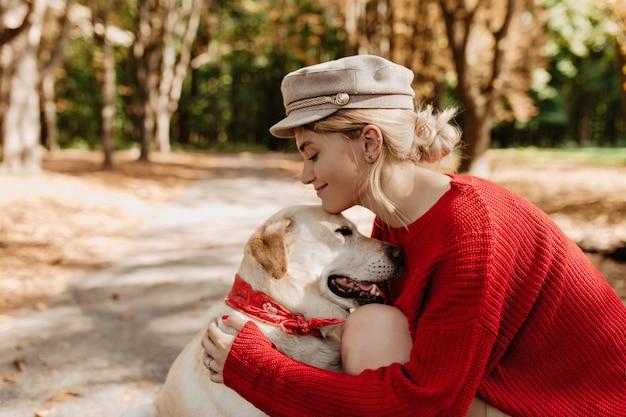 가 공원에서 그녀의 사랑스러운 래브라도 미소 유행 빨간 옷에 젊은 금발. 사랑스러운 소녀와 그녀의 강아지는 야외에서 휴식을 취합니다.