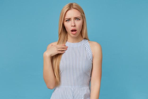 Молодая блондинка с длинными волосами, держащая руку на груди, позирует в полосатом летнем платье, смотрит с растерянным лицом и хмурится