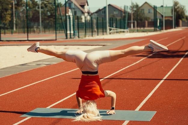 Молодая блондинка учится балансировать в стойке на голове и на руках