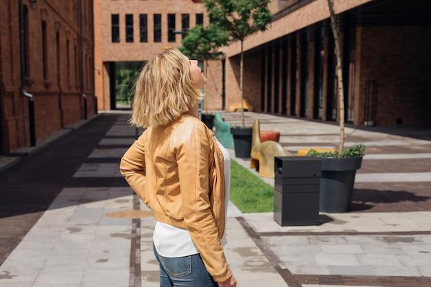 若いブロンドは、シティツーリズムと喜びの街の建築物に興味を持って見えます...