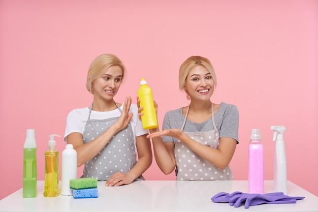 Giovani casalinghe bionde adorabili che indossano guanti di gomma mentre si prepara per le pulizie di primavera Foto Gratuite