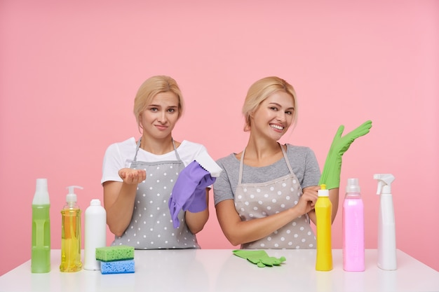 Giovani casalinghe bionde adorabili che indossano guanti di gomma mentre si prepara per le pulizie di primavera