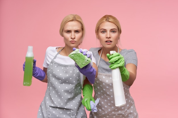 Young blonde lovely housewives wearing rubber gloves while preparing for spring cleaning