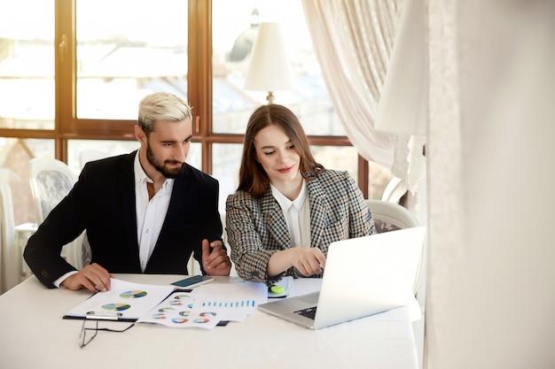 Молодой блондин мужчина и женщина брюнетка смотрят на компьютер и обсуждают бизнес-планы