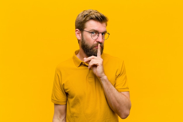 Young blonde man asking for silence and quiet, gesturing with finger in front of mouth, saying shh or keeping a secret  orange wall