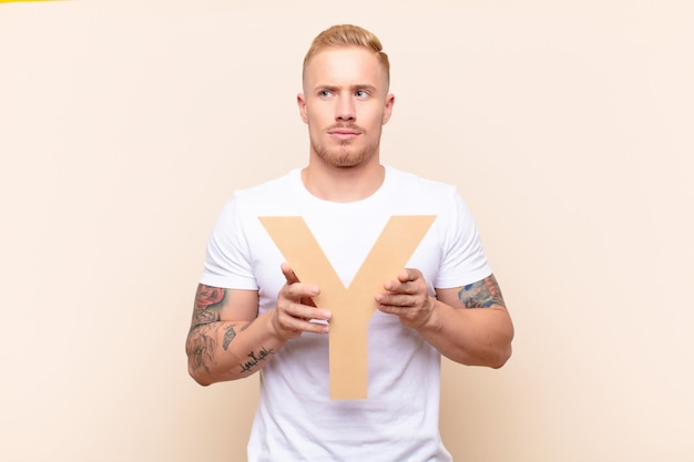 Young blonde man confused, doubtful, thinking, holding the letter y of the alphabet to form a word or a sentence