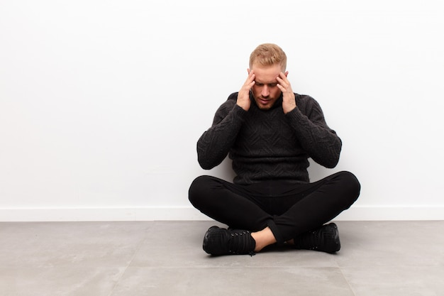 Young blonde man coning eyes with hands with a sad, frustrated look of despair, crying, side view sitting on cement floor