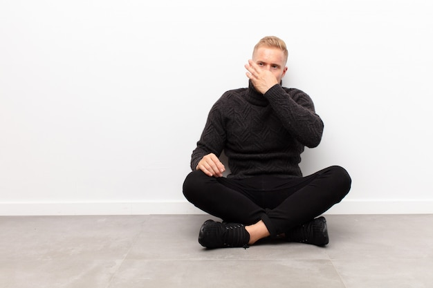 Young blonde man feeling disgusted, holding nose to avoid smelling a foul and unpleasant stench sitting on cement floor