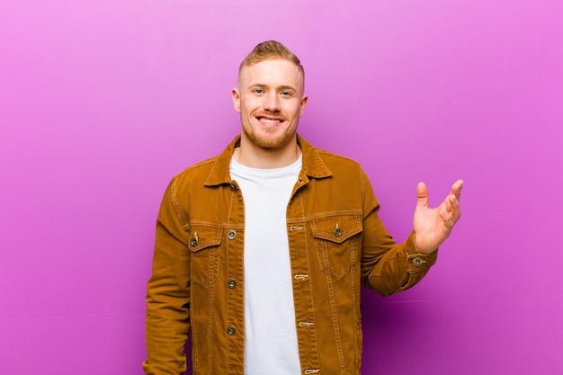 幸せ、驚き、陽気、前向きな姿勢で笑顔、紫色の壁に対する解決策またはアイデアを実現する若い金髪の男