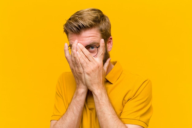 Young blonde man feeling scared or embarrassed, peeking or spying with eyes half-covered with hands on orange wall