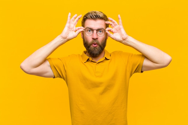 Young blonde man feeling shocked, amazed and surprised, holding glasses with astonished, disbelieving look against orange wall
